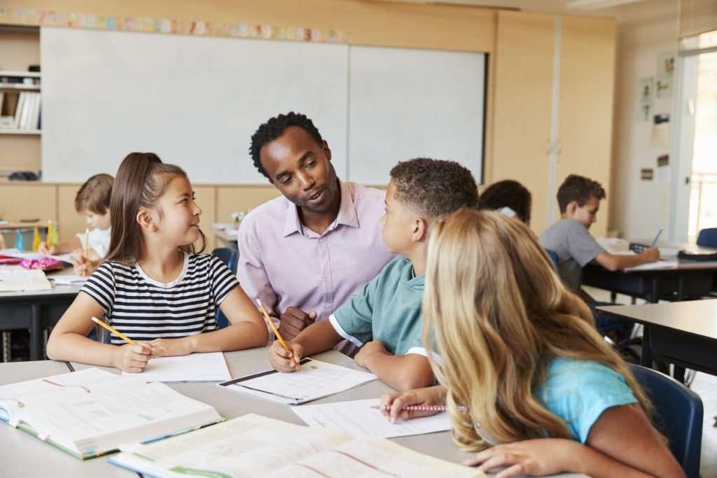 Teacher working with elementary school kids at their desk